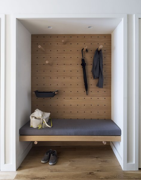 New storage, multifunctional pegs, and pegboards help a New York City lawyer make the most of his 710-square-foot apartment. In the foyer, StudioKCA turned a closet into a valet area.