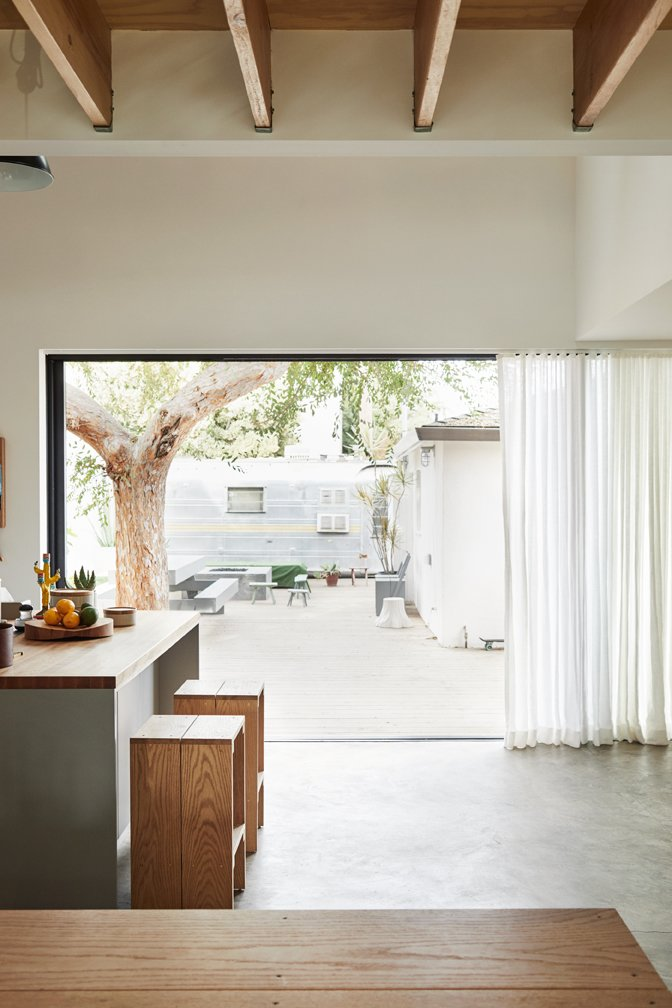 Dining Room, Table, Stools, Pendant Lighting, Concrete Floor, and Bar Sliders open to a deck and beyond to a 1960s Airstream once owned by sculptor Alma Allen in Joshua Tree. The couple use it for guests.  Photo 5 of 17 in Explore the Japanese-Style Home of Two L.A. Tastemakers