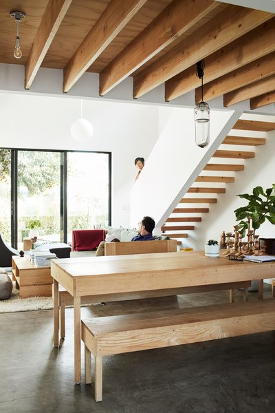 A Peter Ivy pendant hangs over the dining table and benches, also by Taku. At one end is a collection of candlesticks, prototypes for Tortoise that will be manufactured in Hokkaido.  The simple wood treads on the open-riser staircase complement the unfinished ceiling beams.