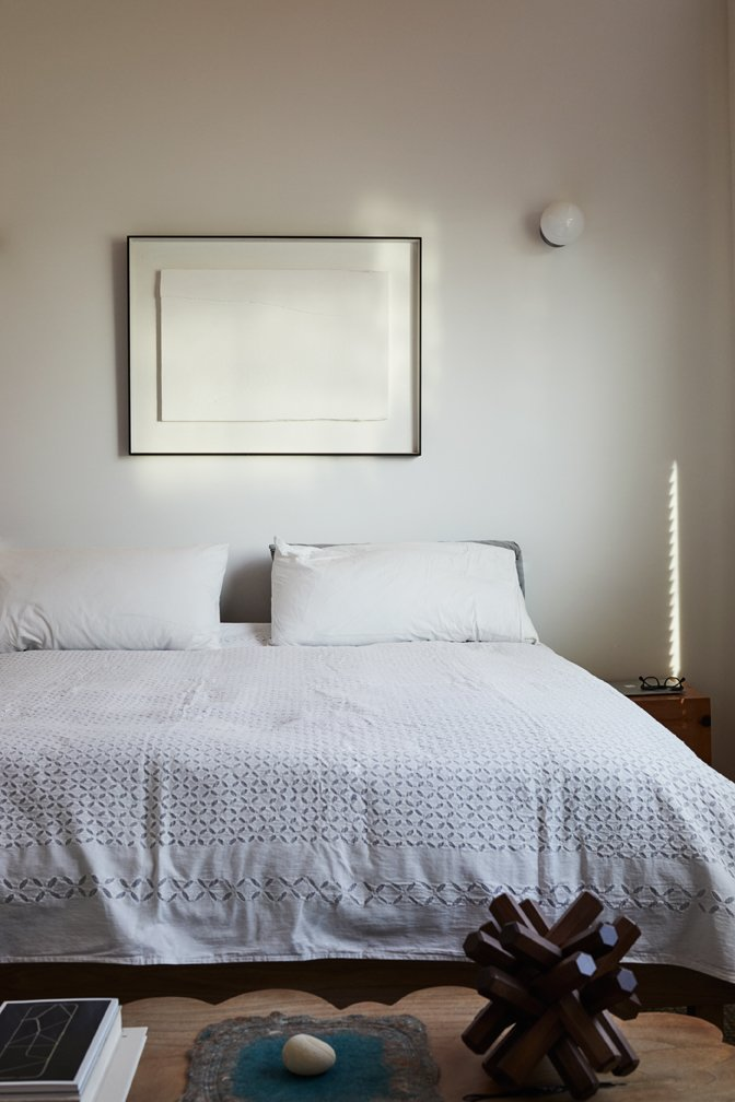 Bedroom, Bed, Wall Lighting, Night Stands, and Bench A scalloped bench by Alma Allen rests at the foot of the bed in the master bedroom.  Photo 9 of 17 in Explore the Japanese-Style Home of Two L.A. Tastemakers