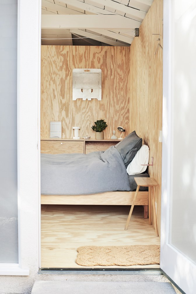 Bedroom, Storage, Plywood Floor, Bed, and Night Stands Pieces by Taku furnish the guest room, which Tanaka converted from the old garage, incorporating straightforward, unfinished materials like plywood.  Photo 12 of 17 in Explore the Japanese-Style Home of Two L.A. Tastemakers