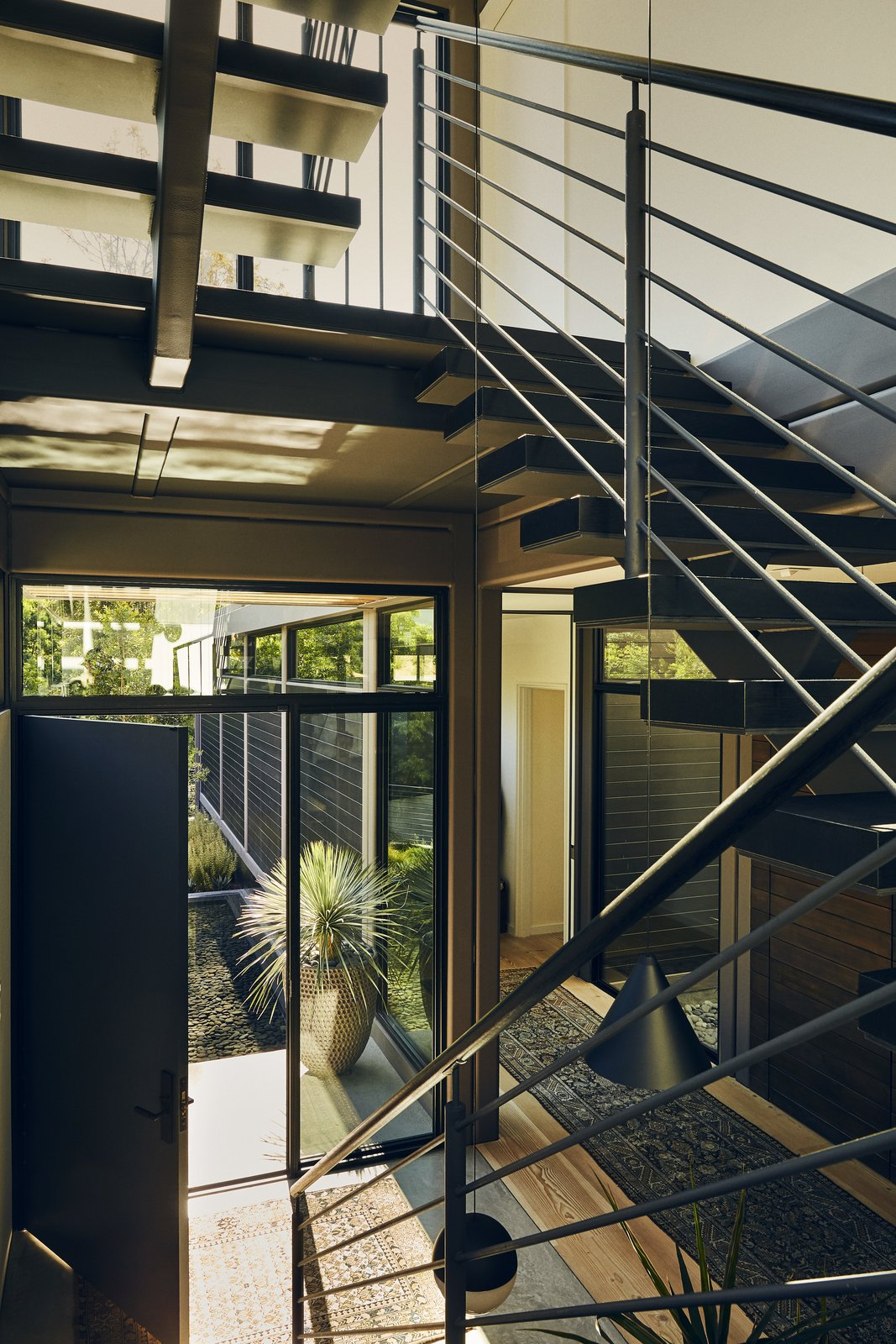 Staircase, Wood, Wood, and Metal Near the front door, charred oak treads float on a blackened steel stringer to the master suite and on to the roof.  Best Staircase Metal Wood Photos from Step Inside Will Arnett's Prefab-Hybrid Home