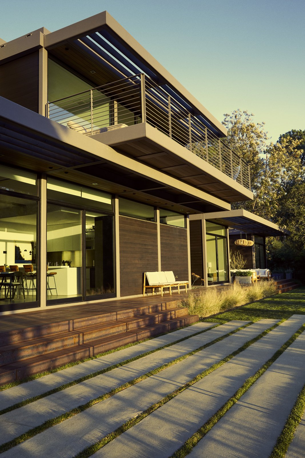 Outdoor, Hardscapes, Grass, and Wood Patio, Porch, Deck Evoking shou sugi ban, the cedar exterior has a Benjamin Moore Arborcoat stain.  Photo 13 of 20 in Step Inside Will Arnett's Prefab-Hybrid Home