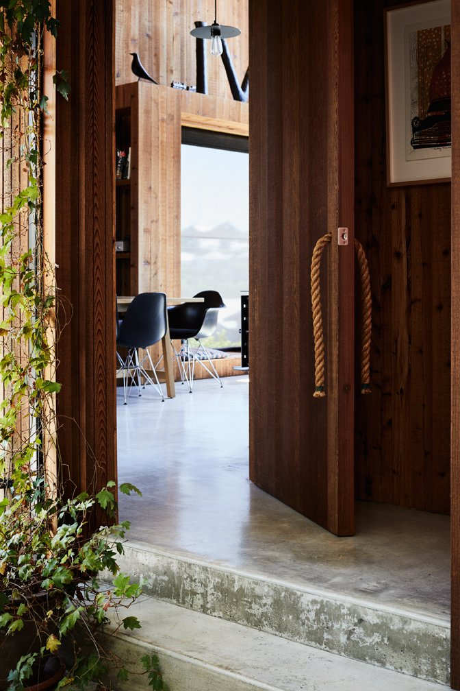 Doors, Exterior, Wood, and Swing Door Type The rope door pulls are Rich's creation.  Photos from This New Zealand Architect Created a House That Looks Like a Tiny Village