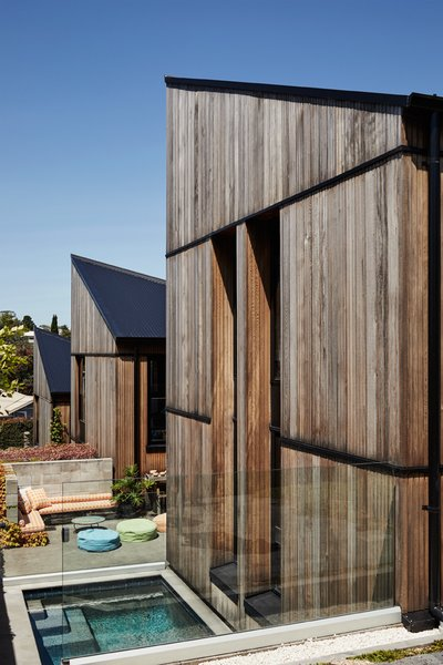 "In Grey Lynn, an Auckland suburb, architect Richard Naish shook up the notion of the Victorian villa that is pervasive here by building a trifecta of pavilions separated by courtyards and ""garden rooms."" The western red cedar facade is offset by the roof's black  galvanized corrugated steel."