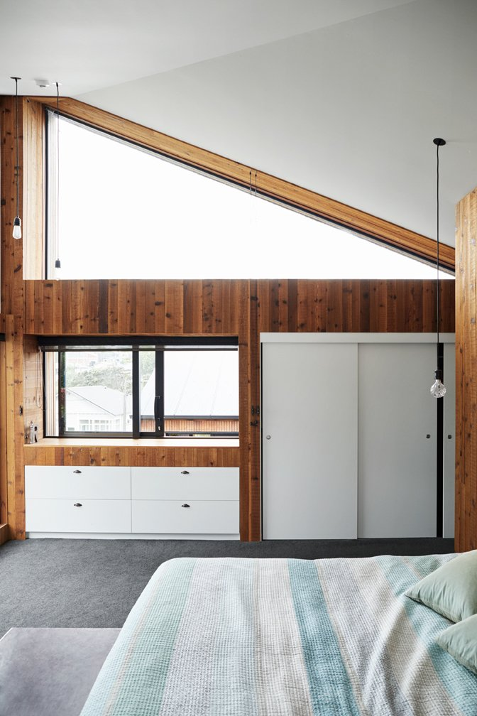 """Bedroom, Dresser, Bed, Pendant, and Carpet In the master bedroom the high triangular window is """"excellent for stargazing,"""" says Rich.  Best Bedroom Carpet Dresser Photos from This New Zealand Architect Created a House That Looks Like a Tiny Village"""