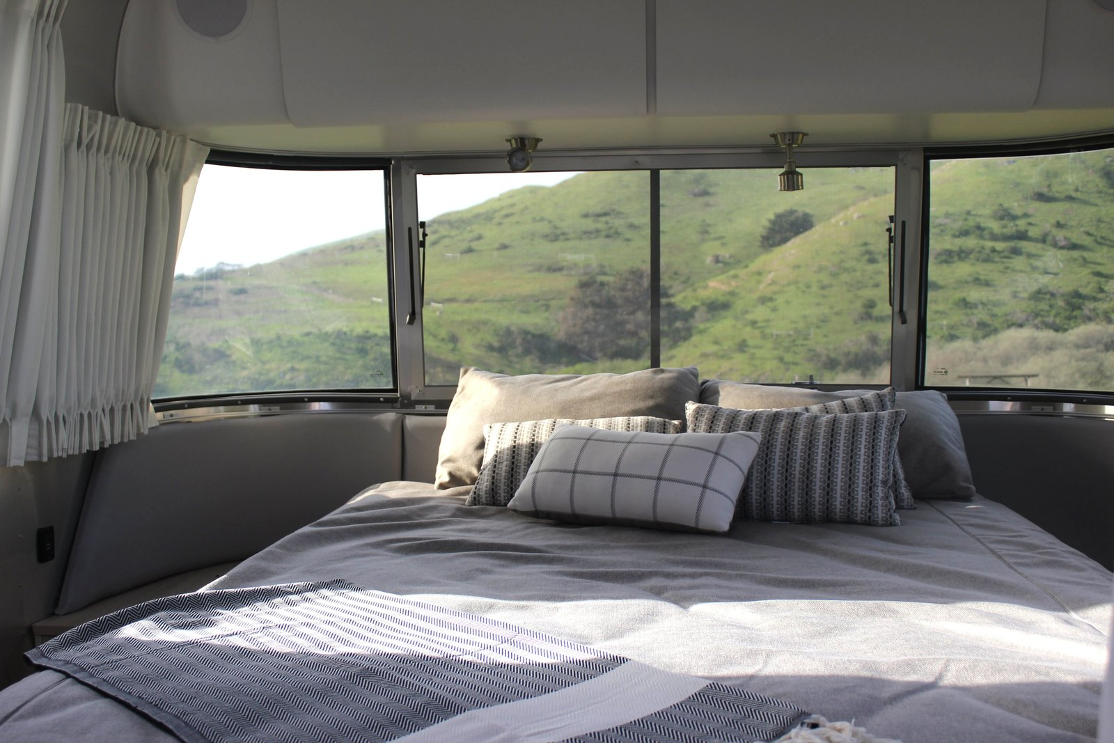 Bedroom, Bed, and Ceiling Lighting Panoramic windows allow the lush hills to act as our headboard, while blackout curtains ensure a good night's sleep. Low-profile nightstands and overhead cabinets offer additional storage.  Photo 6 of 17 in Bodega Bay or Bust: Taking the Airstream Globetrotter to Northern California's Coastal Gem