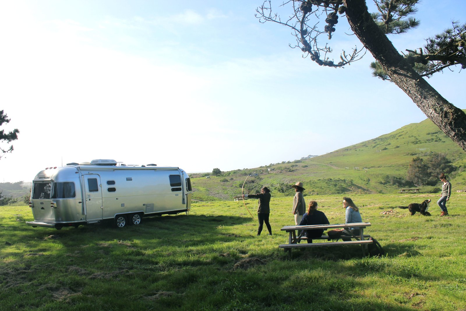 Exterior, Curved RoofLine, Airstream Building Type, Metal Siding Material, and Metal Roof Material Sam and Katie, the hosts at Chanslor Ranch, give us a quick archery lesson.  Photo 11 of 17 in Bodega Bay or Bust: Taking the Airstream Globetrotter to Northern California's Coastal Gem