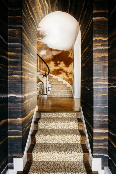 "Inspired by the glinting waters of the San Francisco Bay, a shimmering entrance by Molie Malone greets you as you enter the Marina home. Light bounces off the gold tones in the silk-lined walls with the intention to ""invite you not just to come inside the front door, but to come in and fully explore."""