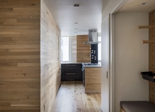 Nearly every kitchen surface is clad in reclaimed white oak. Magnetic spice holders are stuck to a steel column that rises from the counter.