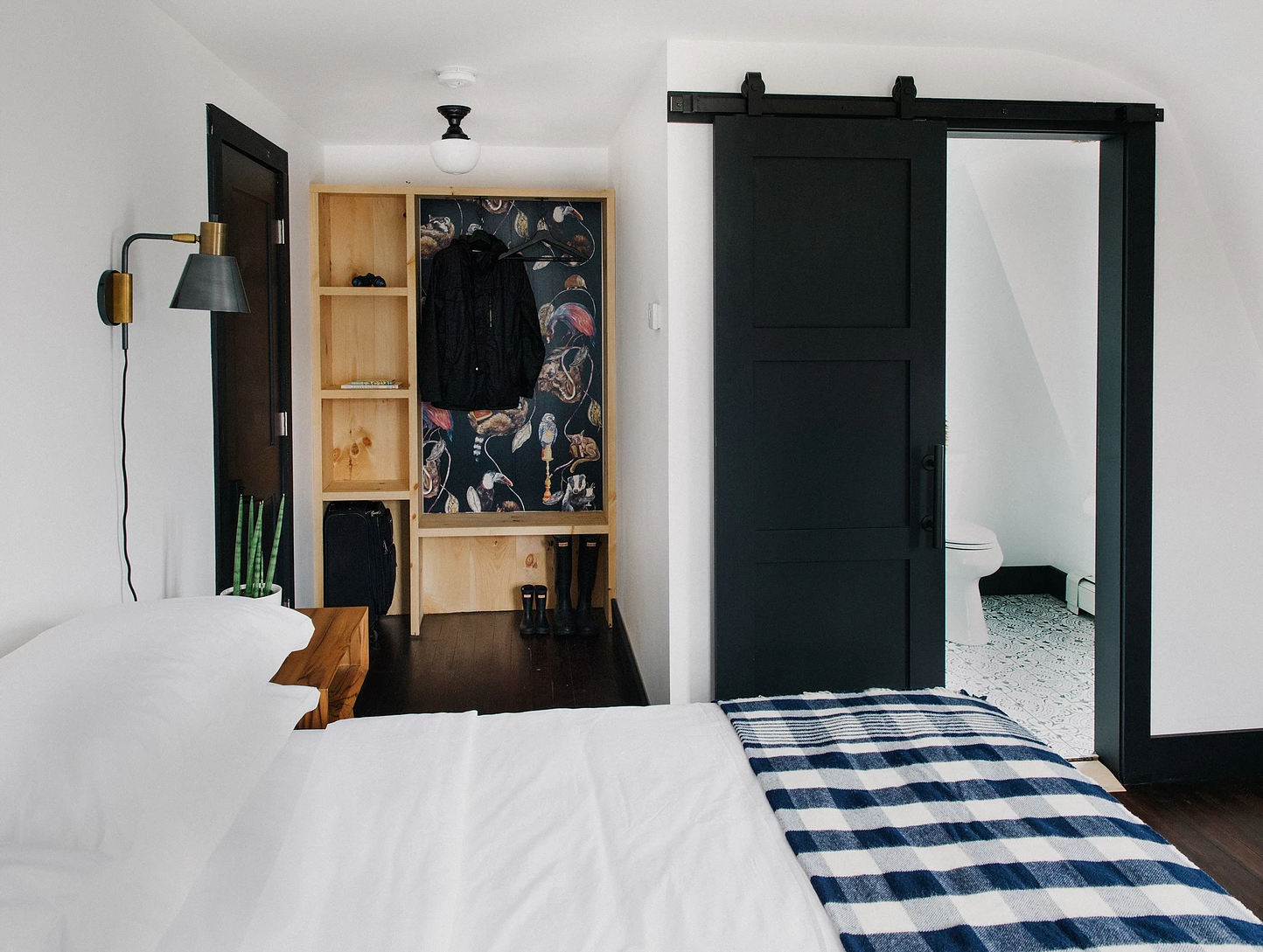 Bedroom, Bed, Dark Hardwood Floor, Night Stands, Ceiling Lighting, Wall Lighting, and Shelves Planked with reclaimed wood and awash in a muted color palette with pops of navy, black and white, the King rooms invoke Scandinavian design energized by the hotel's backcountry.  Eastwind Hotel & Bar
