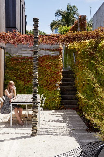 "In the ivy-covered garden on the first level, Alice, 16, sits near ""Rakaia 2,"" a rock sculpture by New Zealand artist Chris Booth."