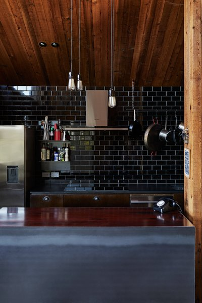 """Rich designed the pendant lights, made of cut plate steel paired with Edison bulbs, partly to economize. """"Each unit cost about fifty dollars instead of five hundred,"""" he says."""
