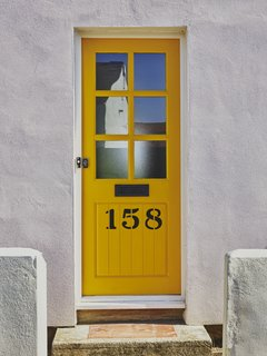 The window frames, side gate, and front door were brightened with custom shades from Johnstone's Paint—a playful blue-yellow-orange color scheme that is carried throughout the house.