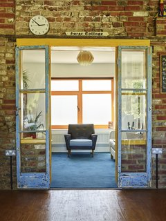 """Architects Tim Ratliff and Tam Landells tripled the footprint of the four-room house and increased the square footage to almost 2,000. Blue doors that were part of the original rear wall connect the """"snug,"""" or sitting room, to the new space. The chair was Natasha's step-granddad's; the 1960s pendant was found on eBay."""