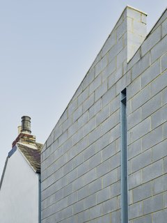 The roofline of the addition has a double pitch; a tall, slim window punctuates the side. High sand content in the mortar gives it a yellowish tint that contrasts with the bricks.