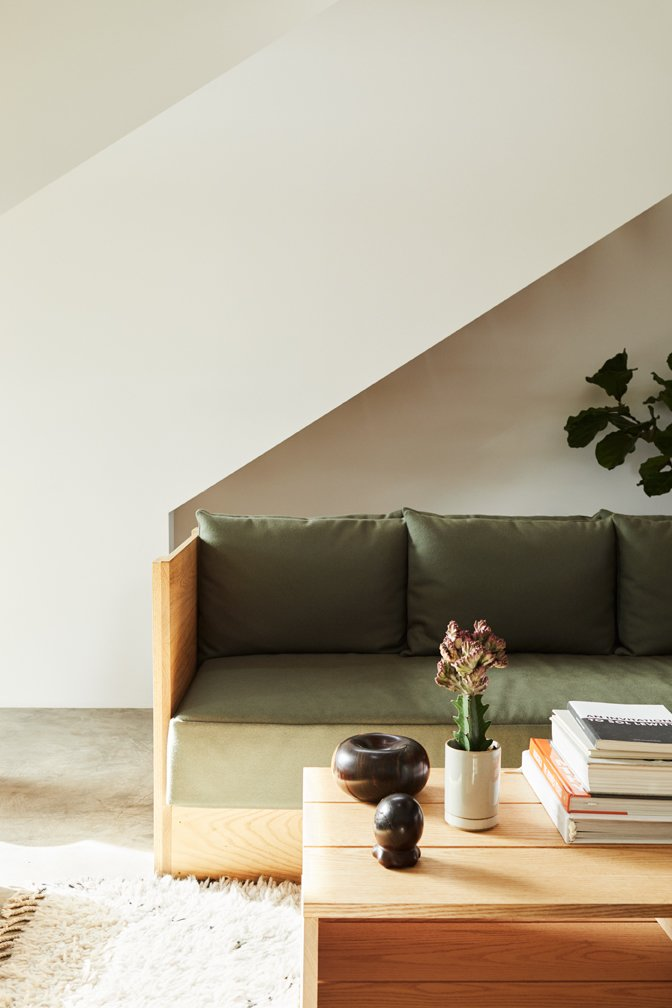 Living Room, Coffee Tables, Concrete Floor, Rug Floor, and Sofa White walls and concrete floors provide a pared-down setting for Taku's oak furniture.  Photo 2 of 17 in Explore the Japanese-Style Home of Two L.A. Tastemakers