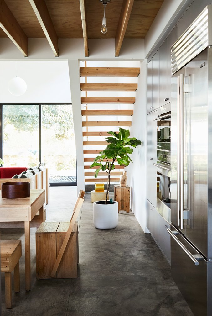 Kitchen, Wall Oven, Ceiling Lighting, Concrete Floor, and Refrigerator The appliances are by Sub-Zero Wolf.  Photo 3 of 17 in Explore the Japanese-Style Home of Two L.A. Tastemakers