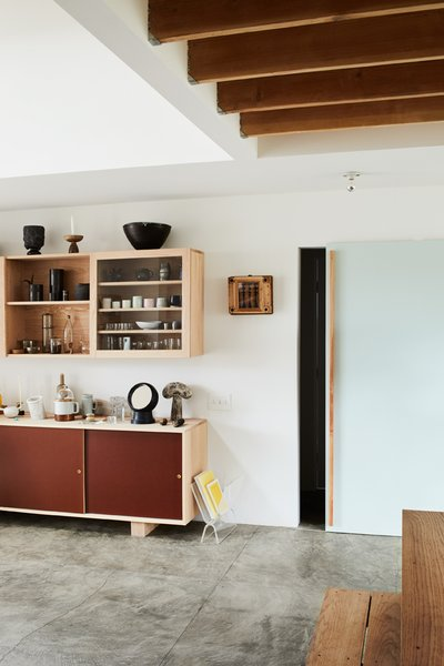 A sliding door conceals an office/guestroom, laundry, pantry, and bathroom.