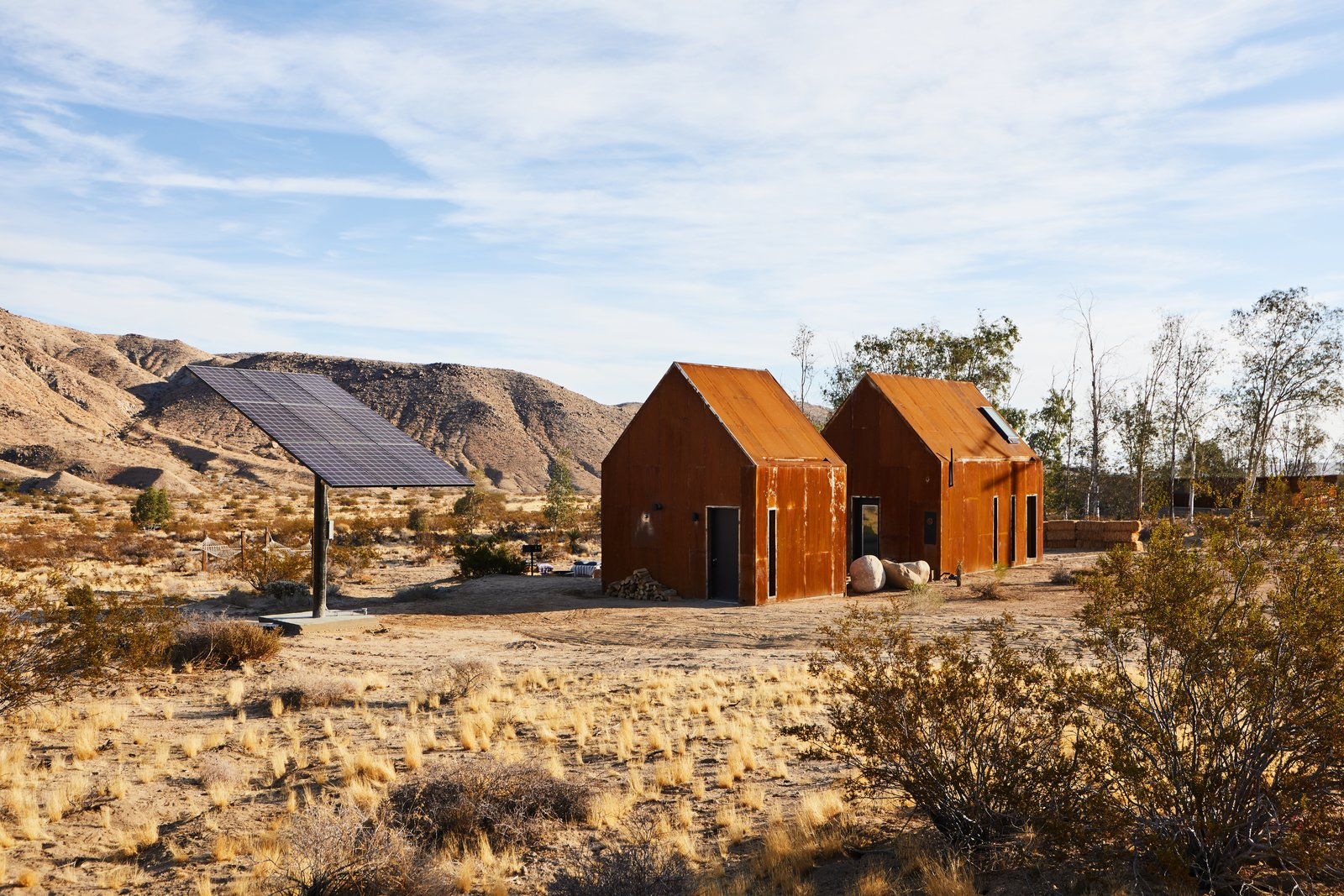 """Exterior, Gable RoofLine, Cabin Building Type, Metal Siding Material, and Metal Roof Material Instead of installing rooftop solar panels, Alqadi and his friend and partner in the venture, Hillary Flur, built a """"solar tree"""" to provide energy.  Photo 8 of 13 in These Tiny, Off-the-Grid Cabins Near Joshua Tree Look Totally Apocalypse-Proof"""