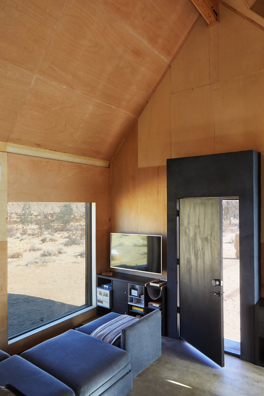 Living Room, Concrete Floor, and Sectional The house has smart locks by August, Caséta wireless controls by Lutron, and a hub security system by Scout.  Photo 9 of 13 in These Tiny, Off-the-Grid Cabins Near Joshua Tree Look Totally Apocalypse-Proof