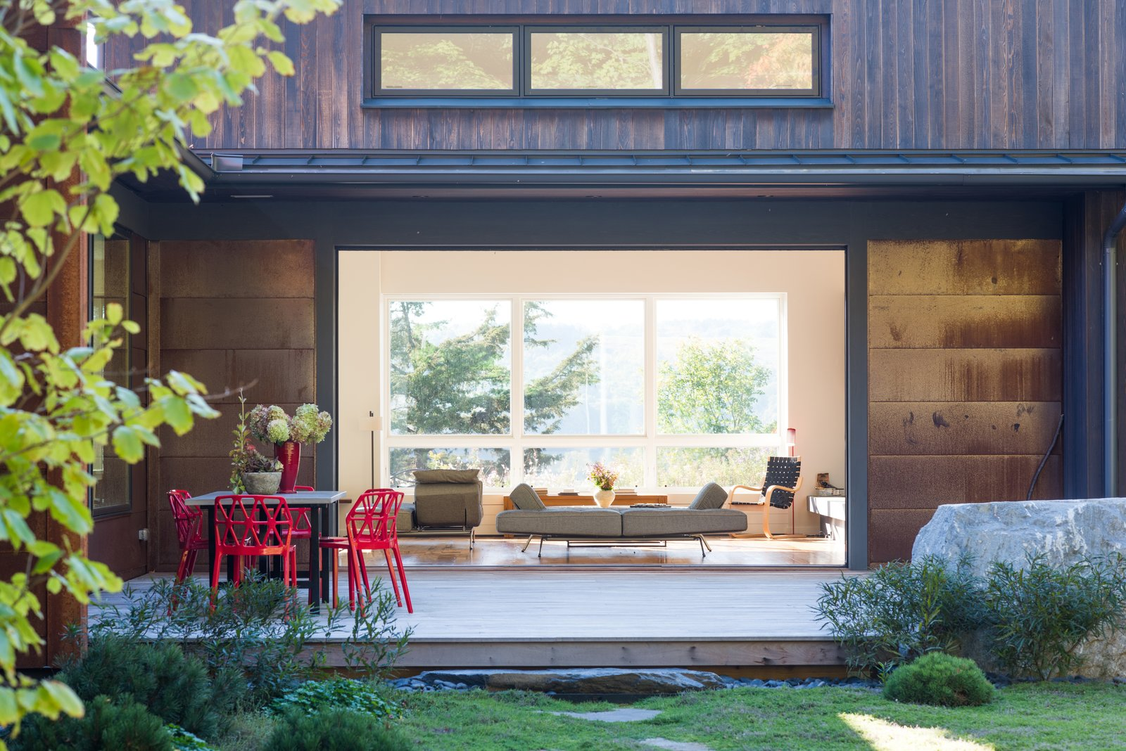 Outdoor, Small Patio, Porch, Deck, Walkways, Grass, Back Yard, and Wood Patio, Porch, Deck Like the windows, the large pocket doors are by Jeld-Wen. Alchemia chairs by Archirivolto are arranged on a deck near the courtyard, which is planted with fragrant thyme.  Photo 3 of 4 in Native Plants Form a Meadow-Like Habitat for a Rustic New York Home