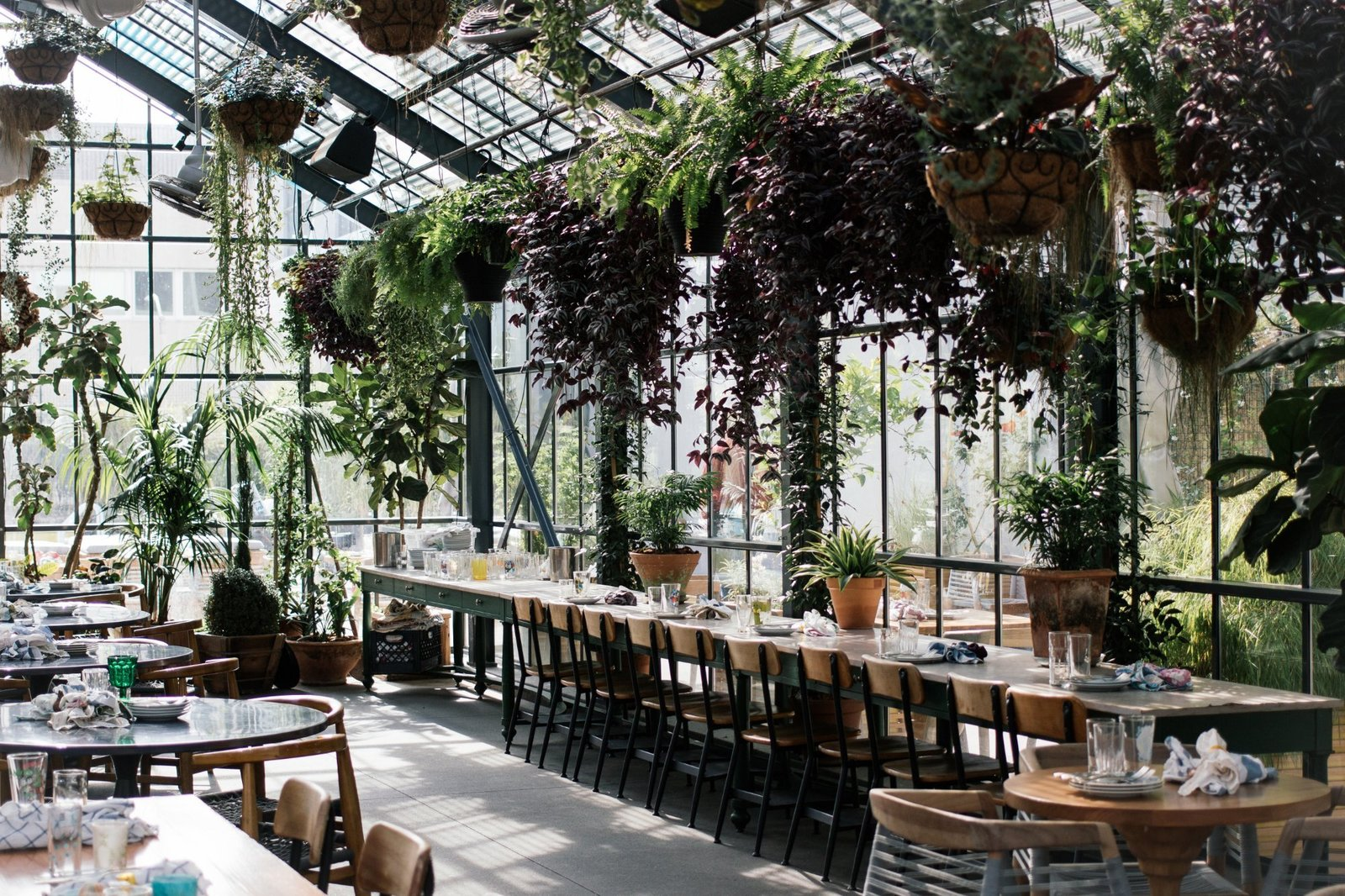 Dining Room, Table, and Chair Next to the shimmering pool on the second floor, the hotel's restaurant Commissary is housed in a lush, urban greenhouse.  Photo 7 of 11 in 10 Greenhouses That Will Inspire You to Grab Your Gardening Tools from The LINE Los Angeles