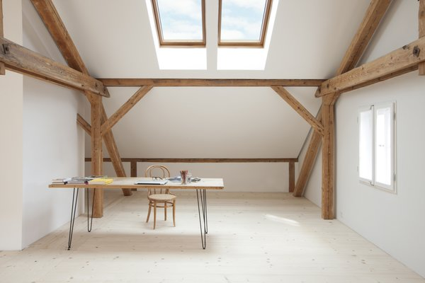 Sunlight streams into Reinhold and Verena's loft through Velux skylights in the pitched roof. Reinhold fastened hairpin legs to an old table to create a desk, pairing it with a bentwood chair. The untreated spruce floorboards—many of which are a foot wide and 14 feet long—come from a stand of trees on the property and were milled on-site. The walls are coated in a custom lime-based paint.
