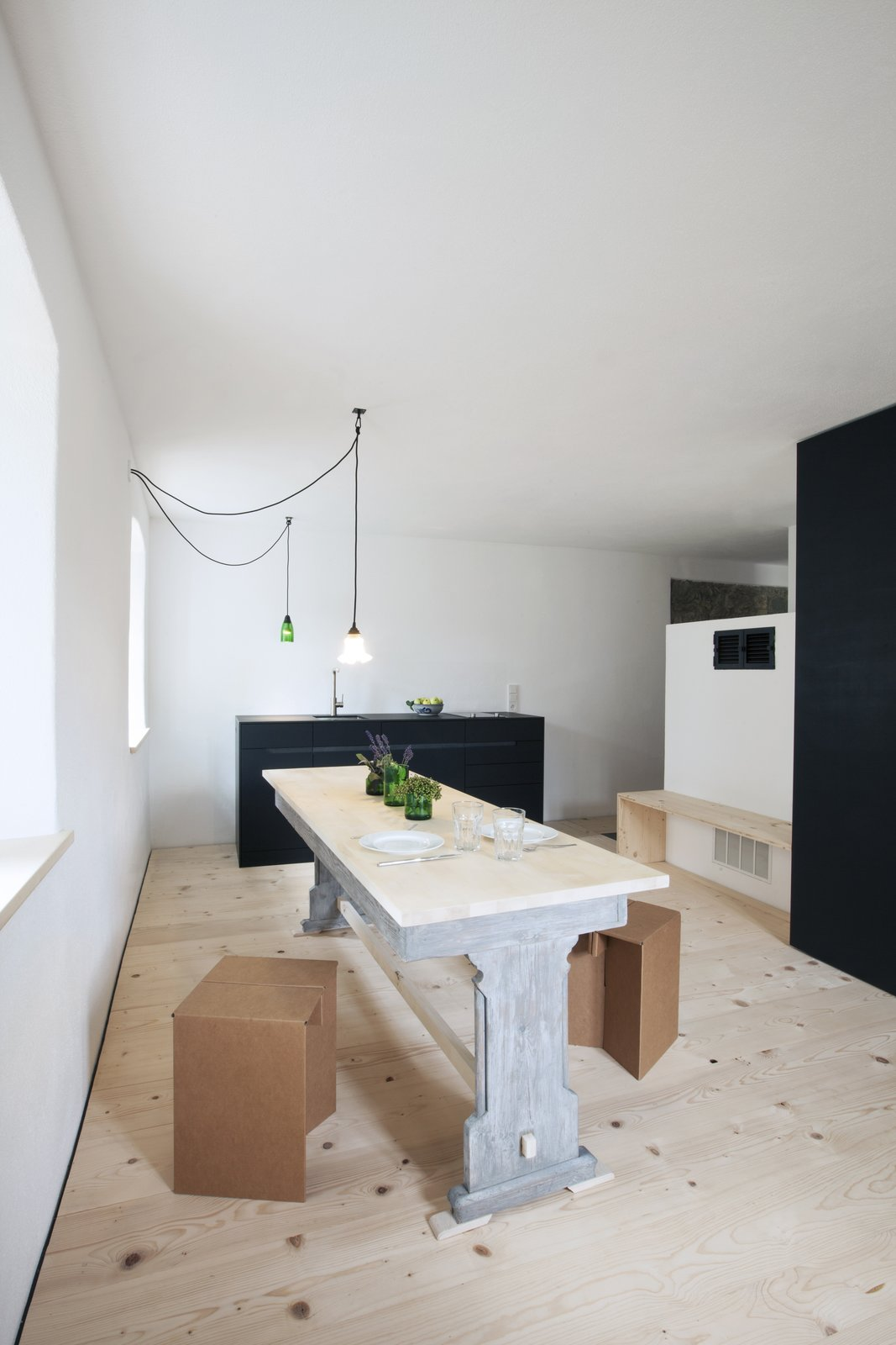Dining Room, Light Hardwood Floor, Stools, Table, Pendant Lighting, and Bench The first-floor rental unit features a table from an 11th-century monastery turned pub.  Best Photos from You Can Rent a Room in This 19th-Century Bavarian Farmhouse, Which Just Got a Minimalist Refresh