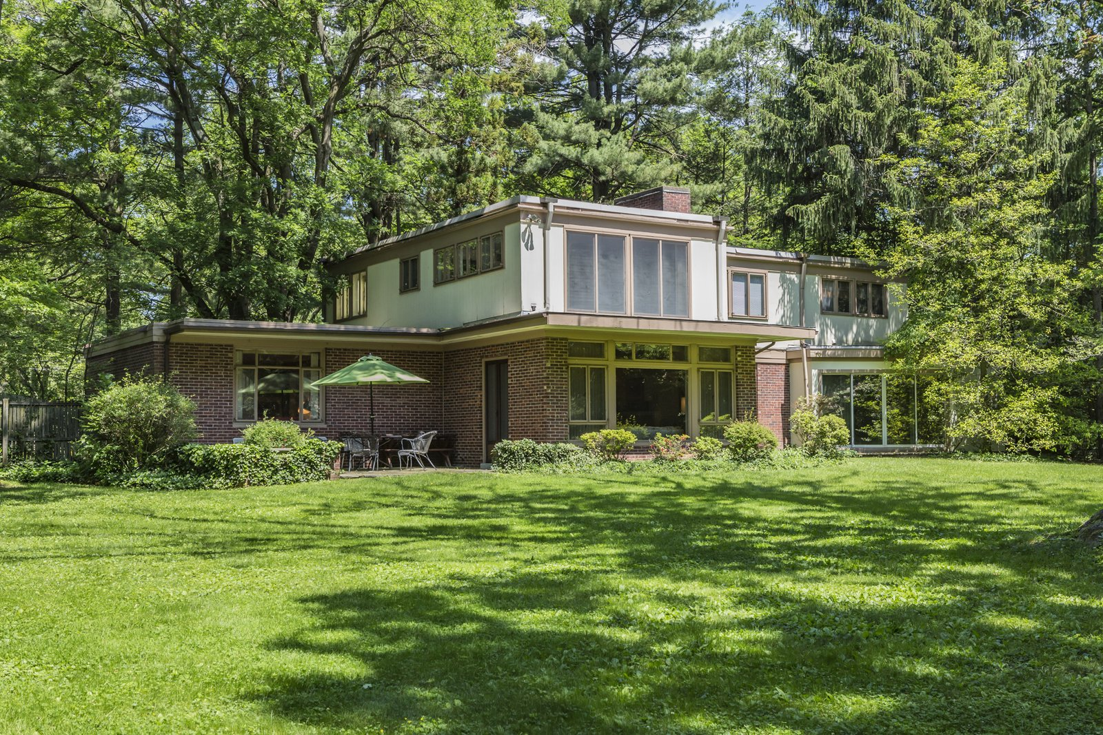 The home's stone patio sits on the idyllic, emerald-green back yard.  Photo 2 of 9 in This Historic, Secluded Midcentury Home is on the Market for $1.2M