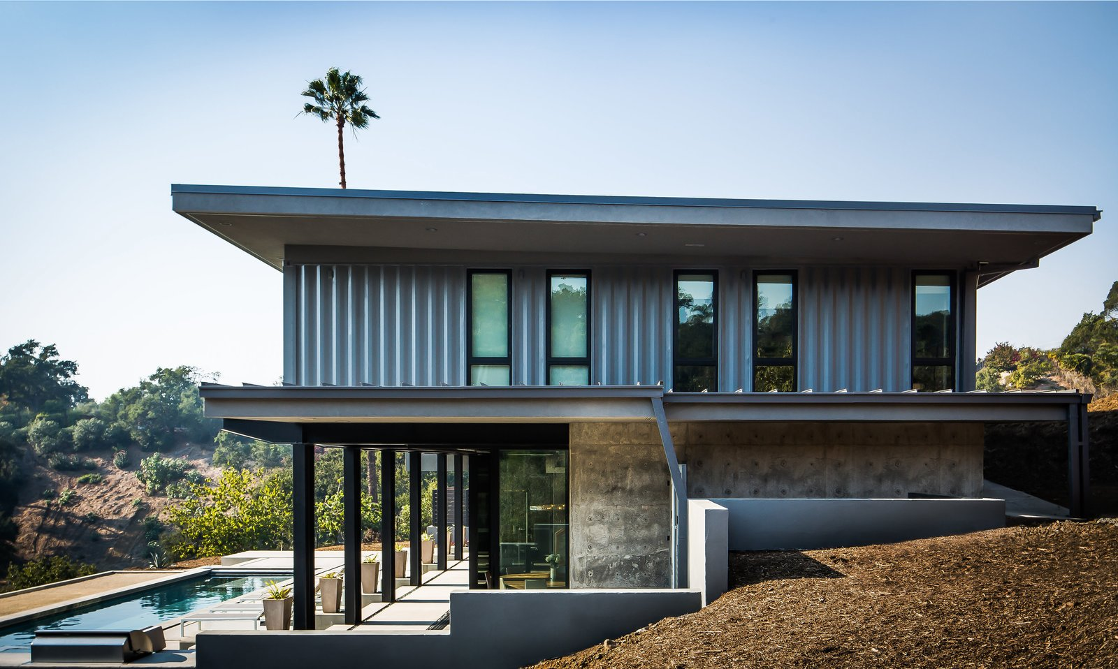 Exterior, Shipping Container, Metal, House, and Concrete The site-built lower level, erected by Barber Builders, connects to the terrace via corner glass pocket doors.  Best Exterior Shipping Container House Photos from Five Shipping Containers Are Woven Into This Home in Santa Barbara