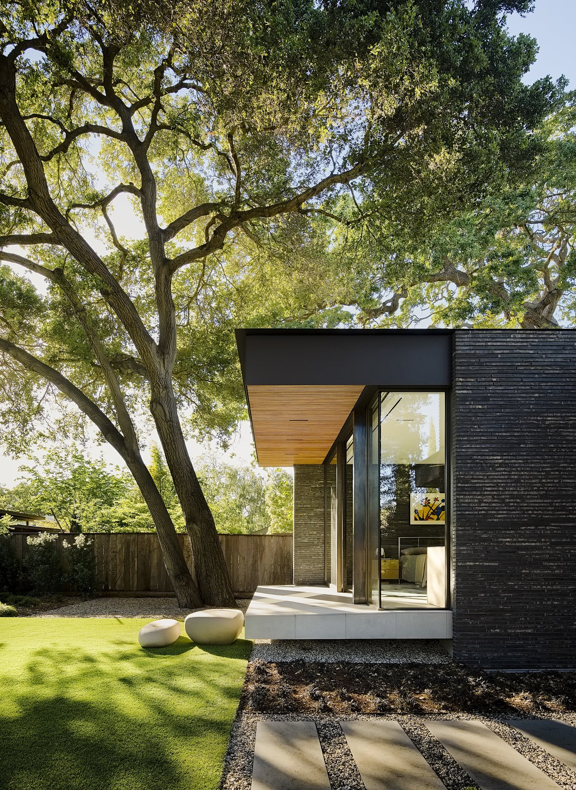Outdoor, Trees, Side Yard, Back Yard, Boulders, Grass, Walkways, and Wood Fences, Wall The master bedroom was raised and cantilevered so as not to disturb the mature oak tree roots. Boulders are used as steps to the lawn.  Photos from A Modernist Dream Home Makes the Most of a Rare Double Lot in Palo Alto