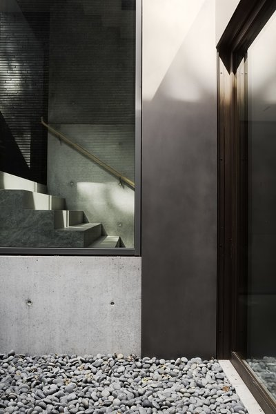 The staircase, which runs from the lower level to the third floor, is lined by a single 32-foot-tall pane of glass.