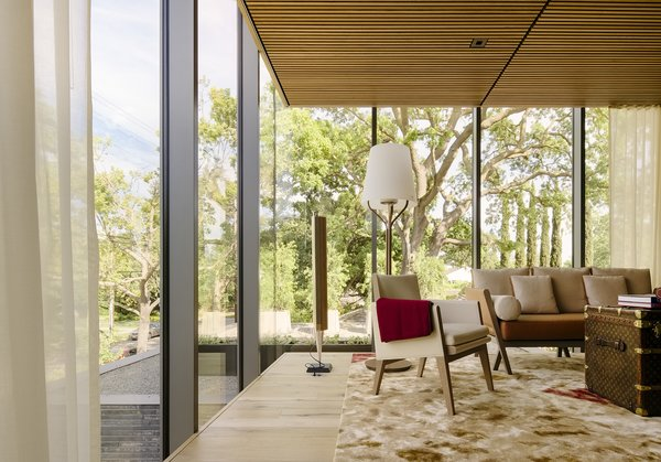 """Oak floors, neutral furnishings, and an area rug by Han Feng for Tai Ping warm the office, as does the view of surrounding treetops. """"You really feel as if you're in the canopy,"""" says architect Takashi Yanai. A vintage Louis Vuitton trunk serves as a coffee table."""