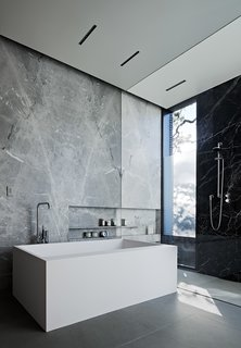 The Statuarieto–walled master bathroom features a Comfort Mood tub by Boffi with taps by Vola; the shower fixtures are by Dornbracht.