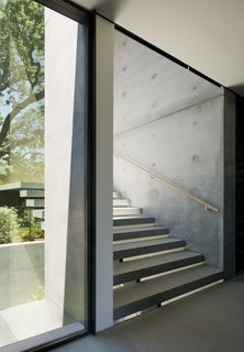 The stair treads are structural steel clad in stone over a steel plate stringer created by West Edge Metals.
