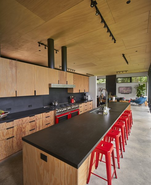 Reminiscent of a shade that Lou's grandfather, an advertising creative, liked to use in his work, the red of the Fred Meyer barstools matches the Bluestar range. A pair of steel-wrapped vents rise from the fir plywood millwork, built by Schuchart/Dow.