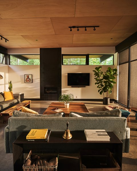 Golden light floods through the Clerestory windows in the living area, accenting the wooden coffee table from Restoration Hardware and the weathered antique bench the couple scored from Robins Egg Bleu in Winthrop, WA.