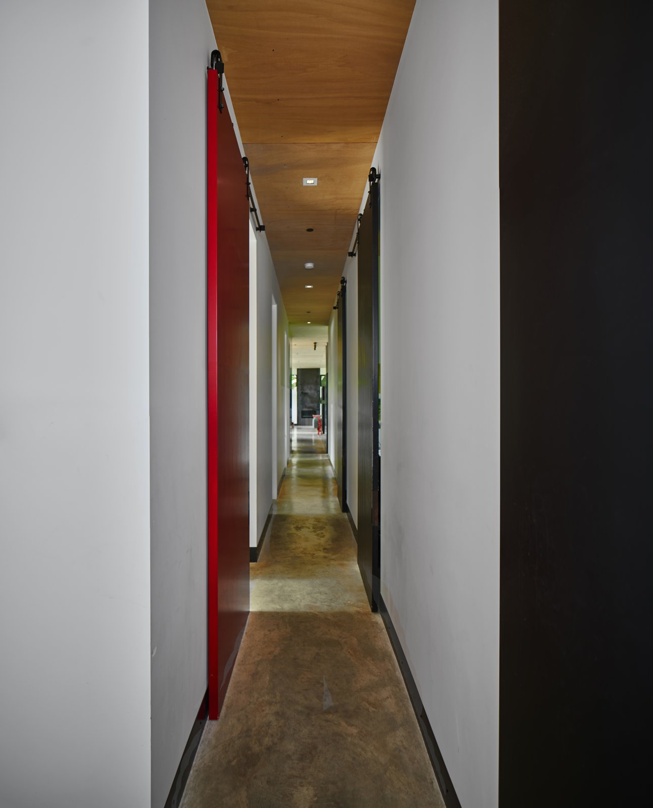 Hallway and Concrete Floor Black and red wooden panels supported by barn door tracks from Richard Wilcox elongate the narrow hallway connecting a series of bedrooms to the living area.  Photo 12 of 18 in A Seattle-Area Family Breaks Free From Suburbia and Ventures Deep Into Nature