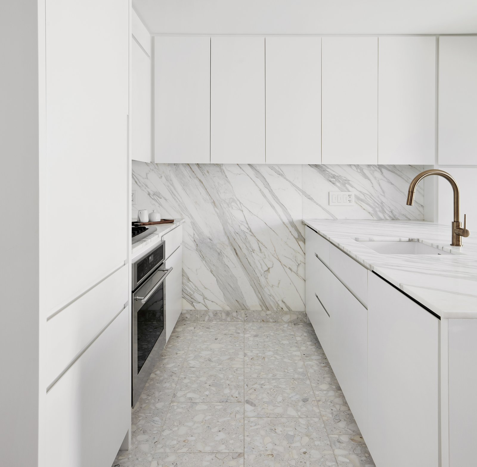 Kitchen, White, Cooktops, Undermount, Wall Oven, Marble, and Marble The kitchen was significantly enlarged; it includes appliances by GE Monogram and a faucet by Delta.  Best Kitchen Cooktops Marble Photos from A Lush Wallcovering Brings the Feeling of Nature Into This Tiny New York Apartment