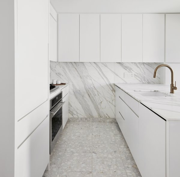 The kitchen of this Manhattan pied-à-terre was opened and enlarged; adding a Calacatta Gold marble countertop and backsplash which runs from just under the cabinets to the terrazzo tile floor that matches the counter's creamy tone.