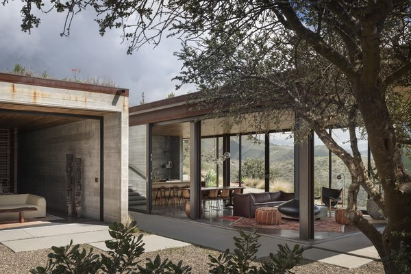 "On an undulating stretch of California coastline, a hidden guesthouse runs free of the grid. ""The house is elemental,"" says project architect Dan Weber of Santa Barbara–based firm Anacapa, who collaborated on the project with designer Steve Willson. ""We endeavored to make it out of materials that would wear and take on a patina over time, so they could feel like part of the landscape."" Unfinished steel, board-formed concrete, and glass continue inside, where rich black walnut—used for ceilings, cabinetry, and furniture—provides an inviting contrast. ""On a foggy day, you want that feeling of warmth around you,"" says Margaret. Brass fixtures complement the deep-hued wood."