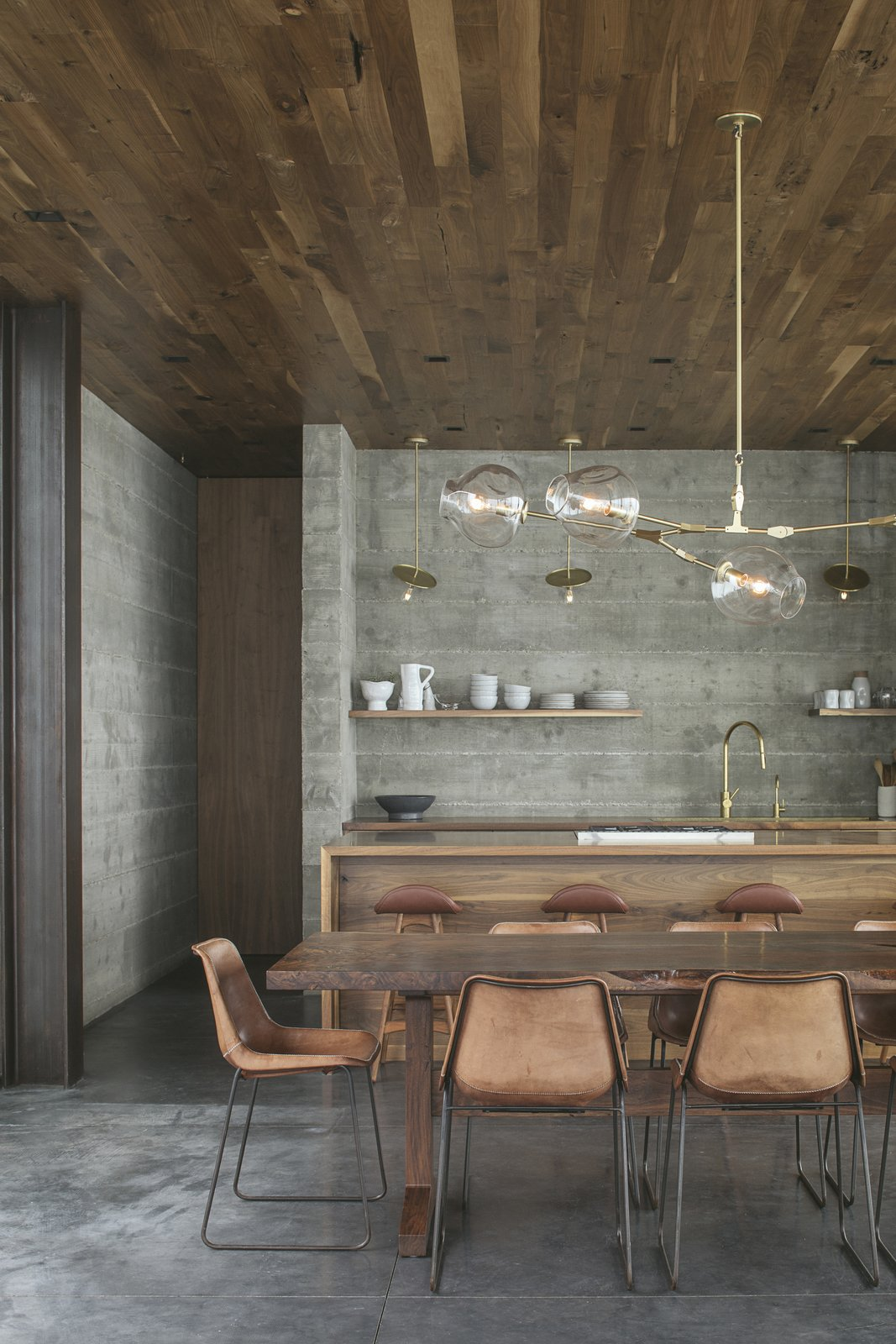 Dining, Table, Pendant, Chair, Concrete, Bar, and Stools Handmade leather Fernando chairs by Jayson Home surround a live-edge custom walnut table by Ben Riddering in the dining area.   Best Dining Photos from A Gorgeous, Off-Grid Guesthouse Perches Lightly on a California Ranch