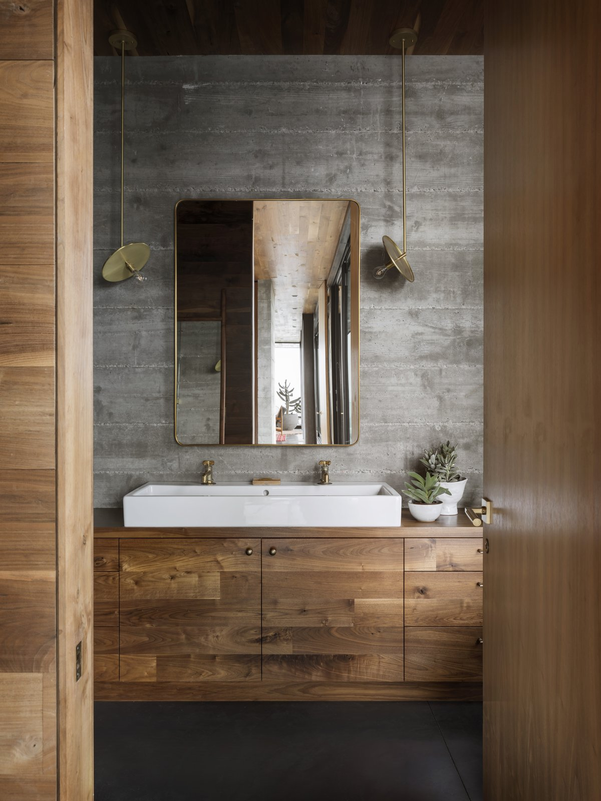 Bath Room, Vessel Sink, Pendant Lighting, and Wood Counter Brass and bronze accents appear throughout the guesthouse, including in the Waterworks taps, Workstead pendants, and Rejuvenation mirror in the bathroom.  Best Photos from A Gorgeous, Off-Grid Guesthouse Perches Lightly on a California Ranch