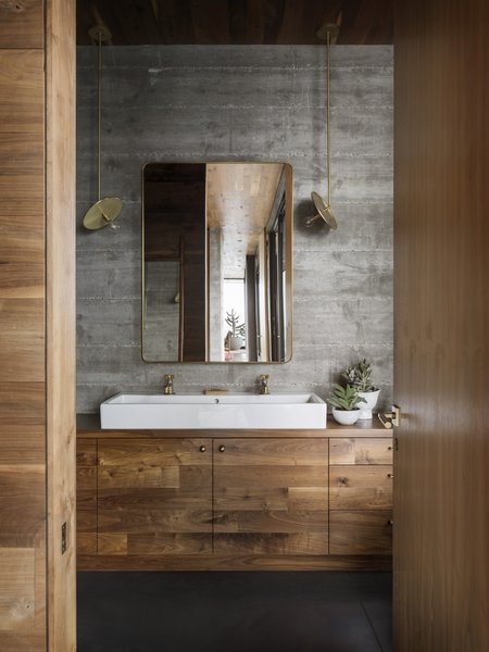 Brass and bronze accents appear throughout the guesthouse, including in the Waterworks taps, Workstead pendants, and Rejuvenation mirror in the bathroom.