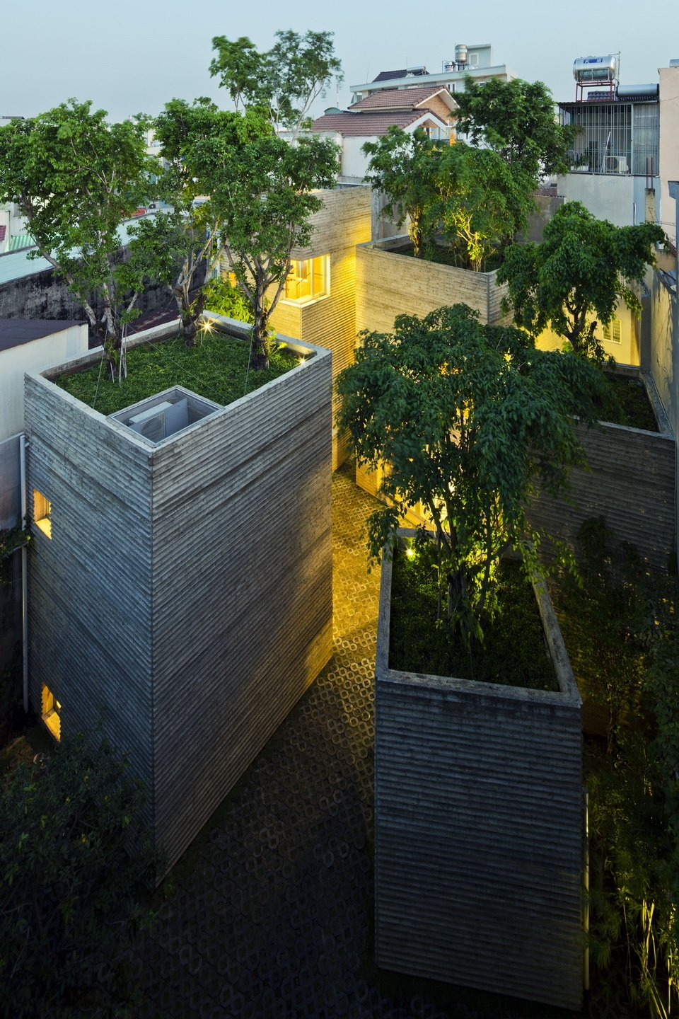 """Outdoor, Landscape Lighting, Rooftop, Grass, and Trees The oasis-like abode stands out amongst the neighboring buildings.  Search """"landscapes--trees"""" from A Concrete Home in Vietnam Is Topped With Trees"""
