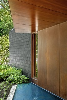 Bluestone slabs lead across a pair of reflecting ponds to the sapele mahogany front door.