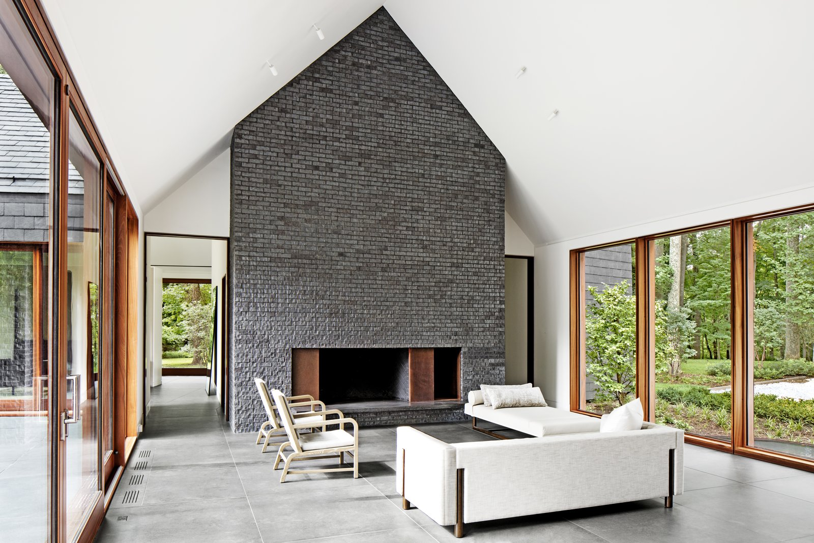 Living Room, Standard Layout Fireplace, Concrete Floor, Ceiling Lighting, Bench, Chair, and Sofa The residence was designed by Baltimore-based architecture firm Ziger/Snead and built by Blackhorse Construction. Its living room features chairs by A. Rudin and a daybed and sofa by Bright Chair.  Photo 3 of 14 in After a Fire, a Maryland Couple Turn to Charred Wood to Rebuild Their House