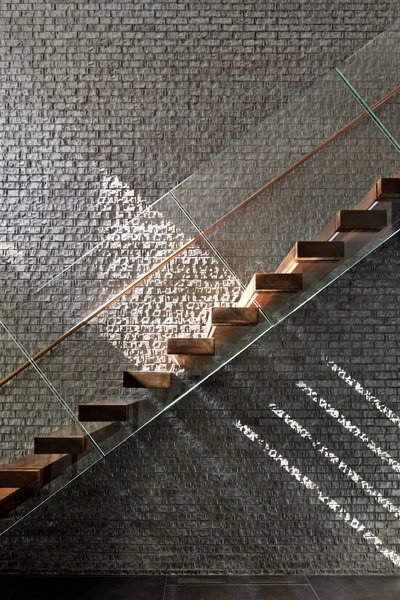 Duratherm windows paint the black brick wall of the staircase with sunlight.