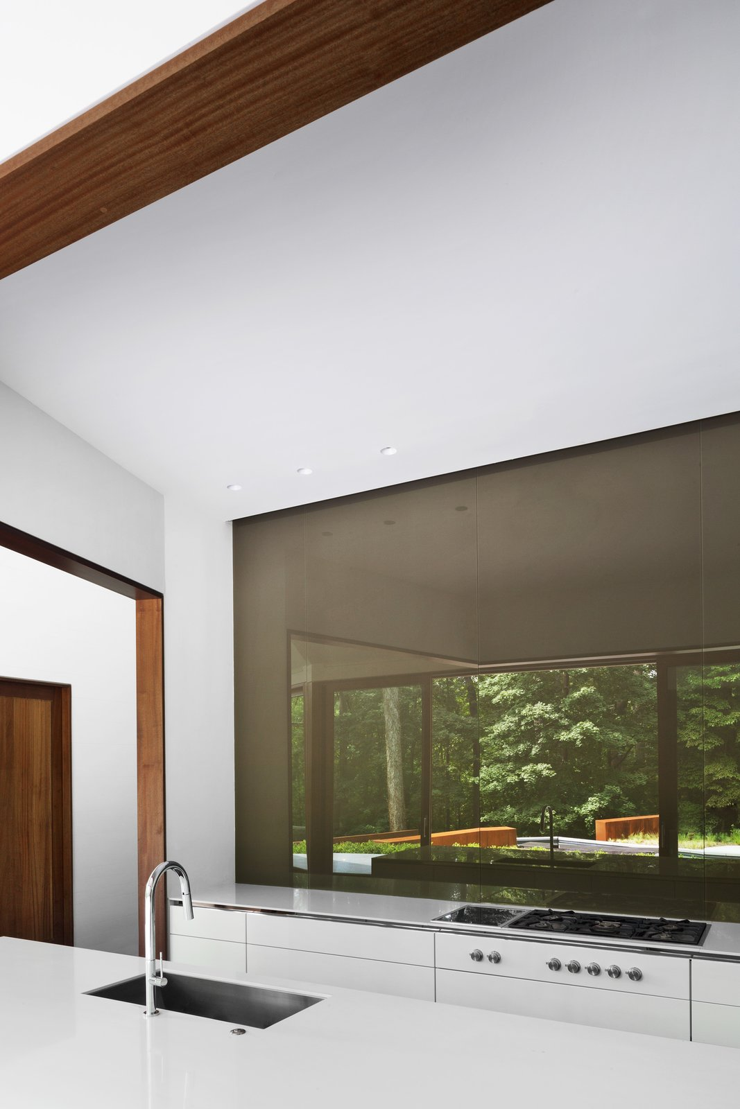 Kitchen, Undermount Sink, Recessed Lighting, Cooktops, and White Cabinet The owners have a wall of reverse-painted glass in the kitchen so they can gaze at the trees as they cook. The faucet is by Brizo.  Photo 7 of 14 in After a Fire, a Maryland Couple Turn to Charred Wood to Rebuild Their House